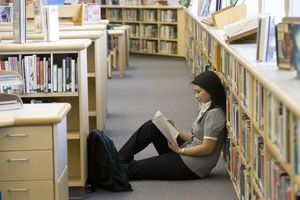 School girl (14-15) reading on floor by bookshelf in library