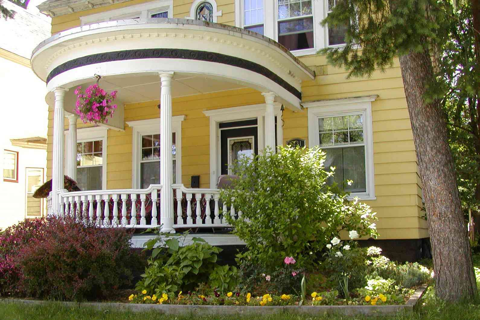 Doric columns on a round porch attached to the front of a yellow house