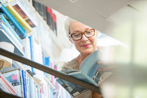 older woman looking through a book in a bookstore or library