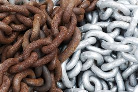 Rusty chains next to non-rusty chains.