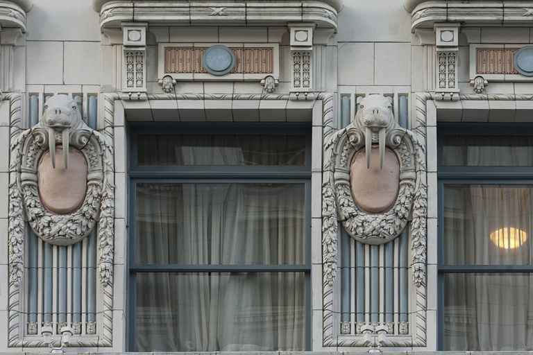 detail facade of ornate windows with terra cotta walrus figures between windows