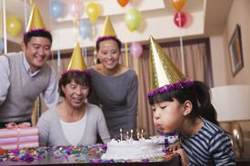 Chinese girl blowing out birthday candles with family