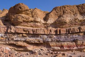 Layers of sedimentary rock in a natural cliff formation.