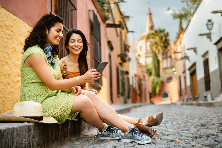 Two women chatting and looking at phone