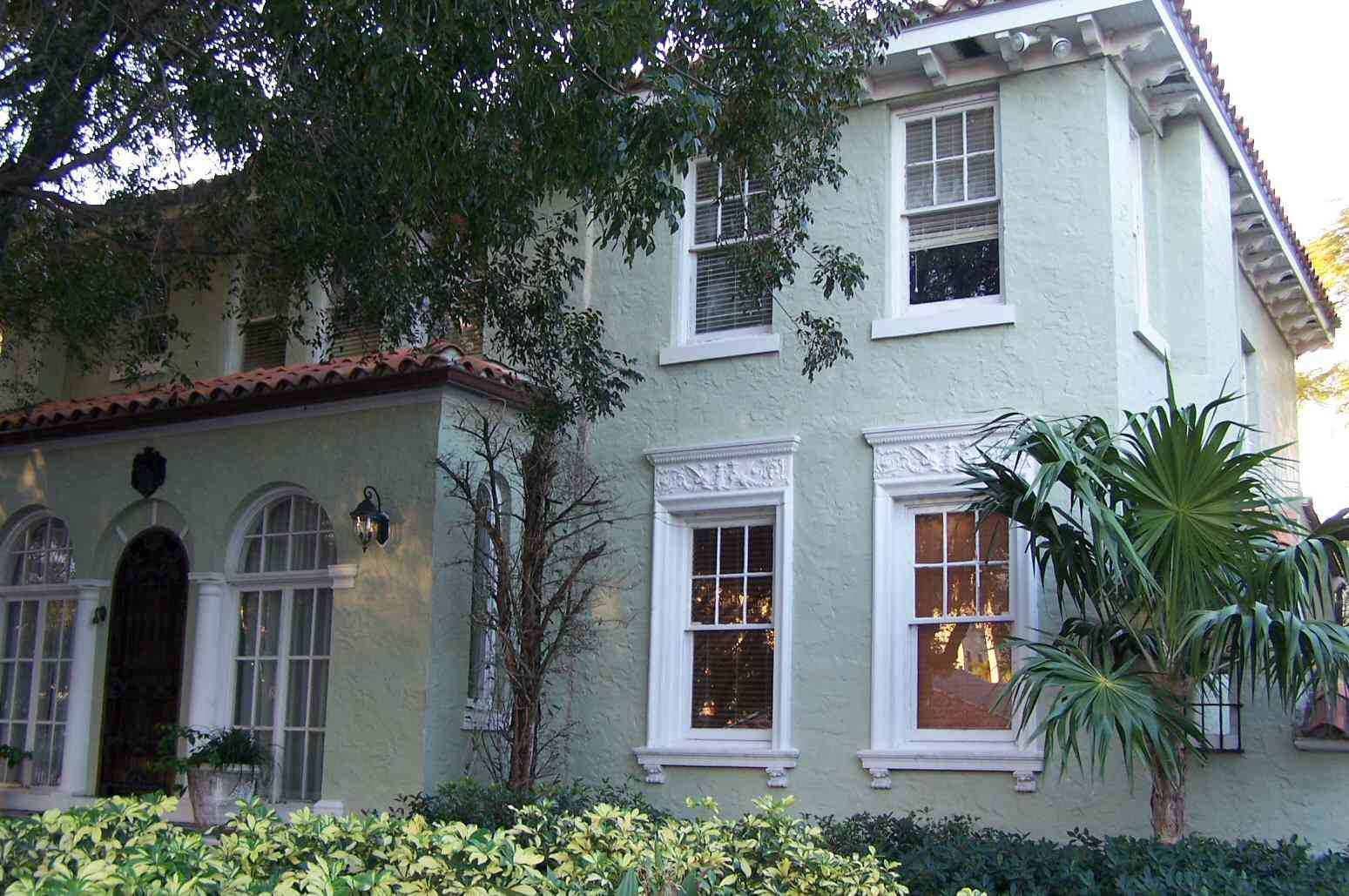 Pale Green Stucco White Trim Two Story Overhanging Eaves Front Entry With