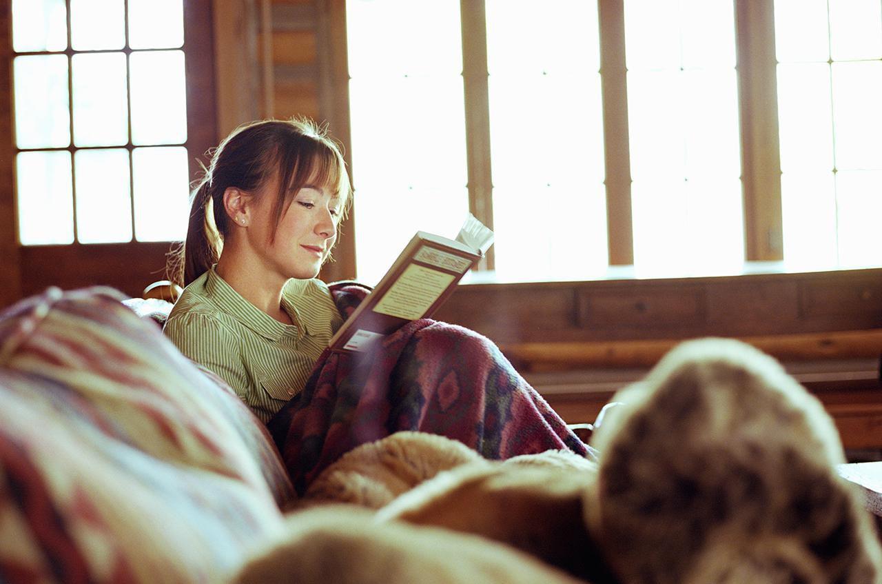 Teenage girl reading book in cabin