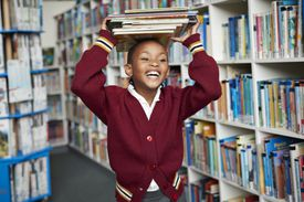 Cute schoolgirl smiling & balancing stack of books on the head at library