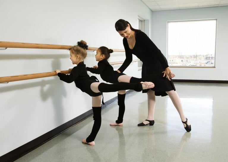 Ballet instructor helping girls perform an arabesque