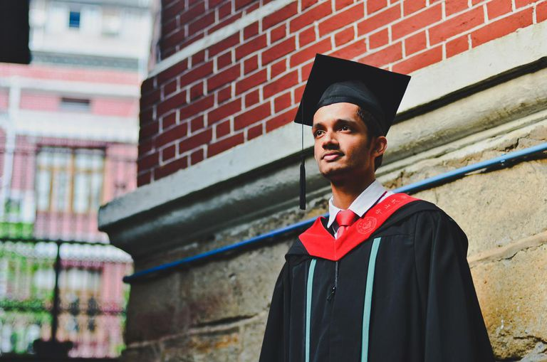 Graduate's portrait against red brick wall