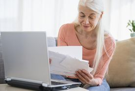 Senior woman going over bills with a laptop