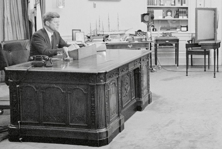 President John F. Kennedy seated at the Resolute desk