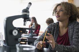 Focused high school student microscope listening science classroom