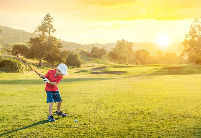 Junior golfer swinging clubs at sunset