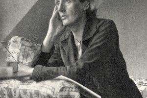 Black and white photograph of Virginia Woolf, seated on a chair and resting her arms on the chair.