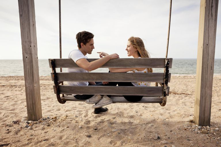 Guy & Girl Sitting on Wooden Swing on Beach