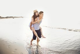 Young man giving piggyback to woman on the beach.