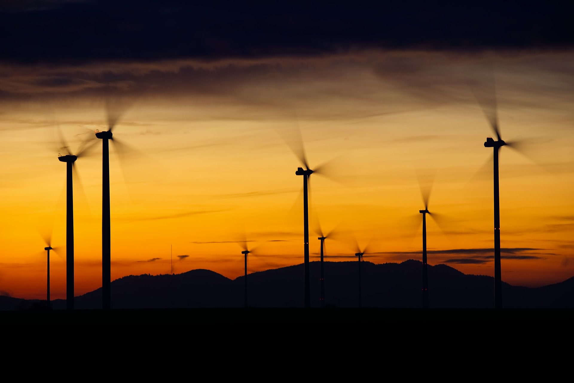 Wind farm with turbines spinning quickly at sunset.