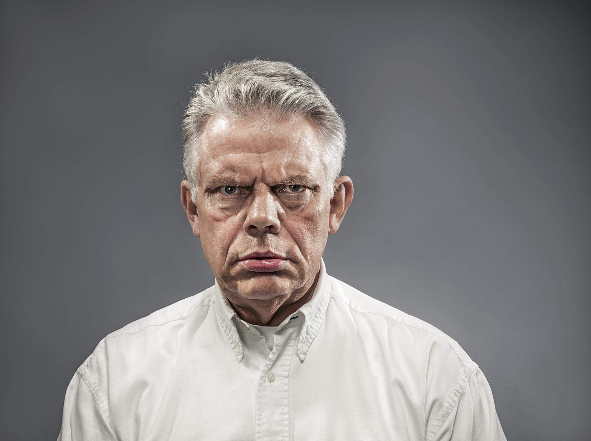 A stern looking man in a white shirt