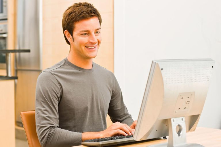 Smiling young man working on computer
