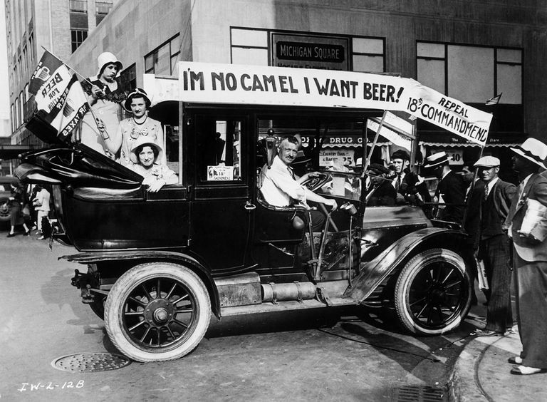 Prohibition protesters parade in a car emblazoned with signs and flags calling for the repeal of the 18th Amendment. One sign reads, I'M NO CAMEL I WANT BEER!