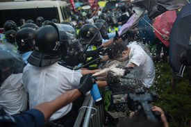 Hong Kong police, representing the political power of the state, spray and beat a member of the Occupy Central with Peace and Love movement, representing Marx's theory of class conflict.