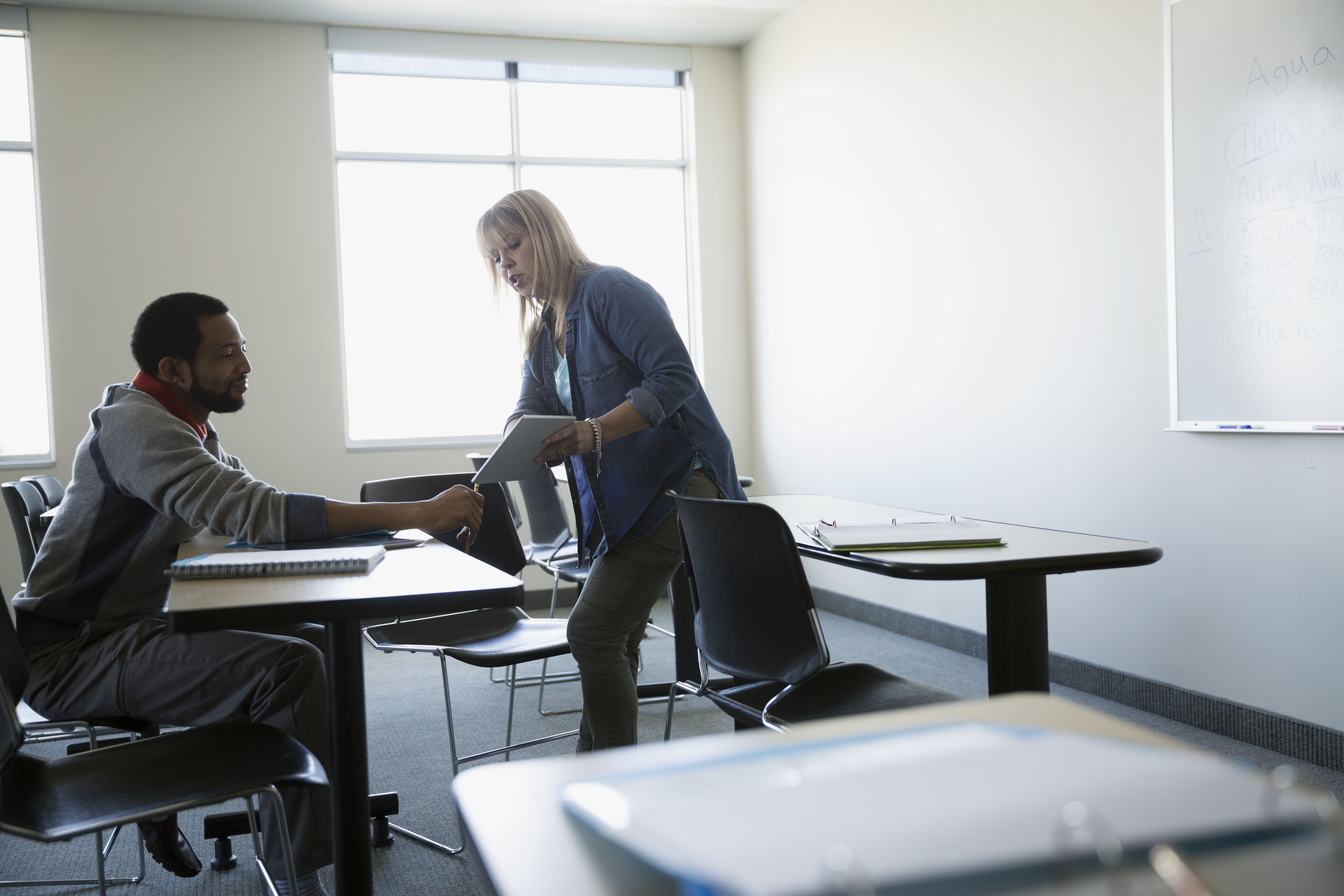 Professor with digital tablet helping adult education student in classroom