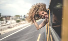 woman with head outside bus on highway