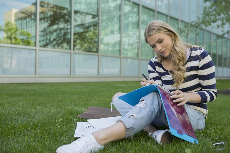 College student doing homework on campus lawn
