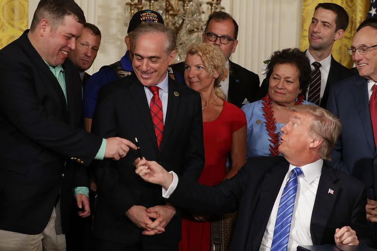 Trump handing over a bill signing pen