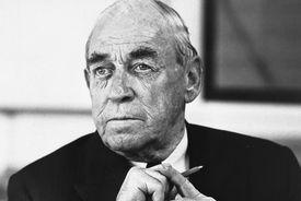Black and white photo headshot of older white man holding a pen