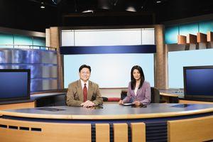 Anchor man and woman at a news desk smiling at the camera.
