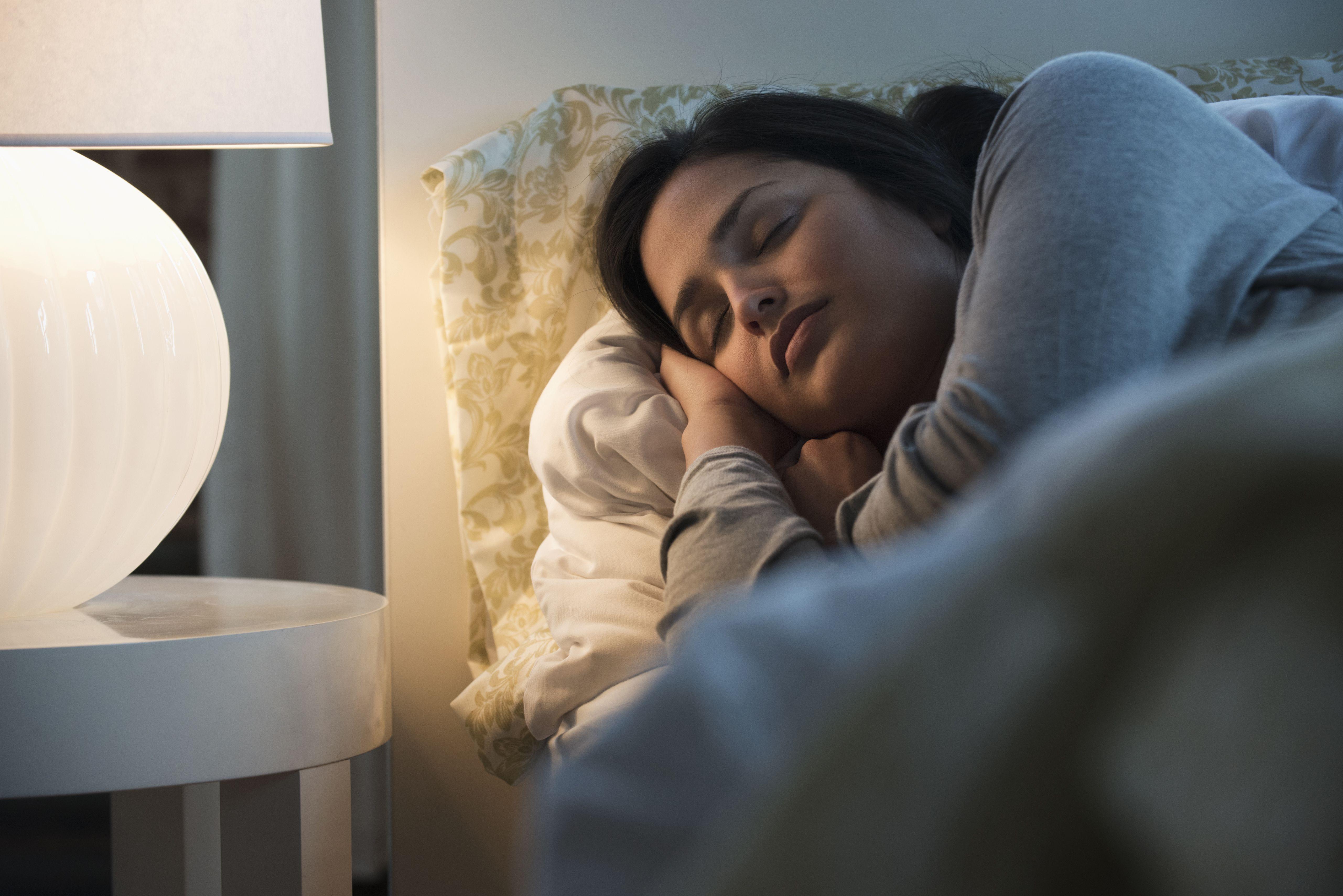 Lamp illuminating a sleeping woman with cozy, dreamy light