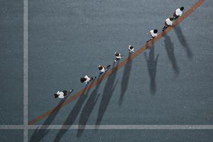 Aerial view of children walking along an upward curving line.