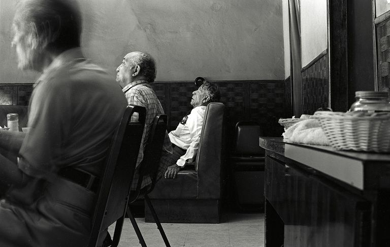 An elderly man sleeps in a cafe