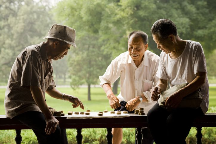 Three men playing board game outdoors smiling