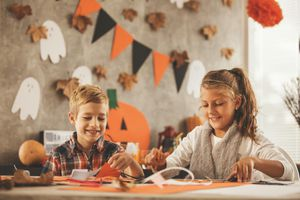 Boy and girl are making decoration for their Halloween party.