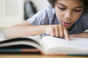 Boy reading book at desk.