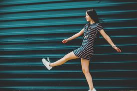 happy brunette young woman walking on street against blue wall