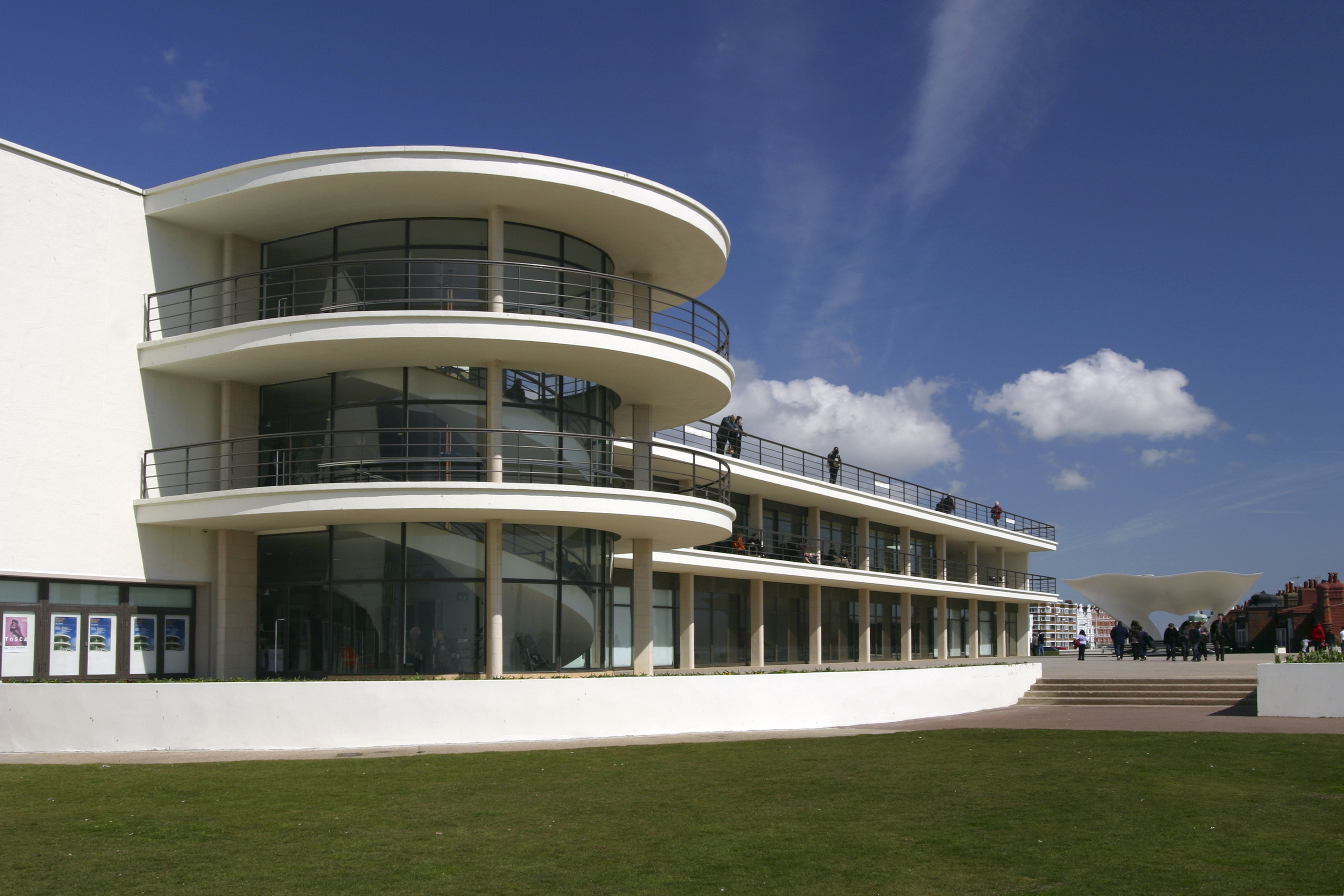 sleek white horizontal oriented building with central disc-shaped glassed balconies