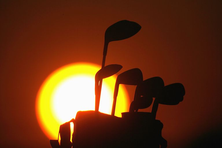 Bag full of golf clubs silhouetted against the setting sun