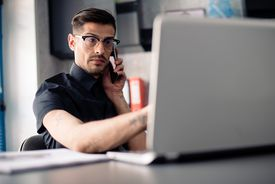 Man in glasses on phone using laptop computer