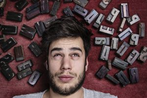 Young man with letterpress letters surrounding his head