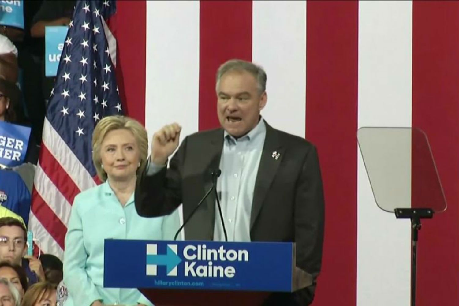 Tim Kaine speaks at the podium while Hillary Clinton looks on