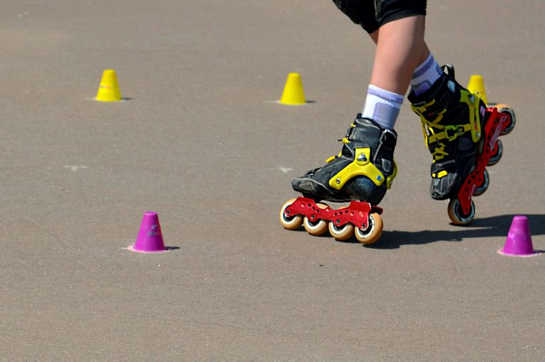 Leggs of roller skating girl training with inline rollerblades.