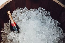 A bottle of champagne in a wooden barrel with ice