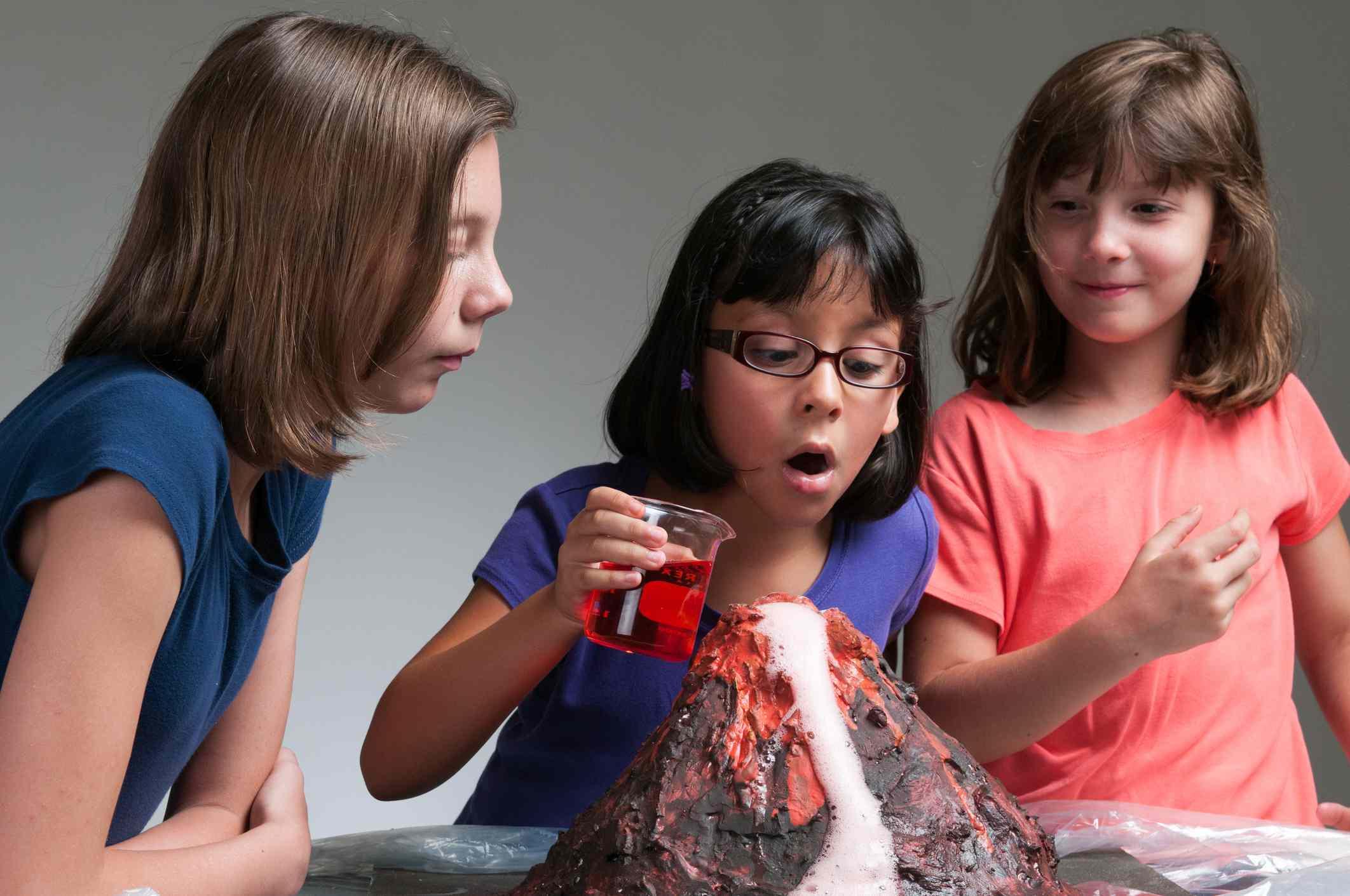 Three young school girls watch a model volcano erupt.