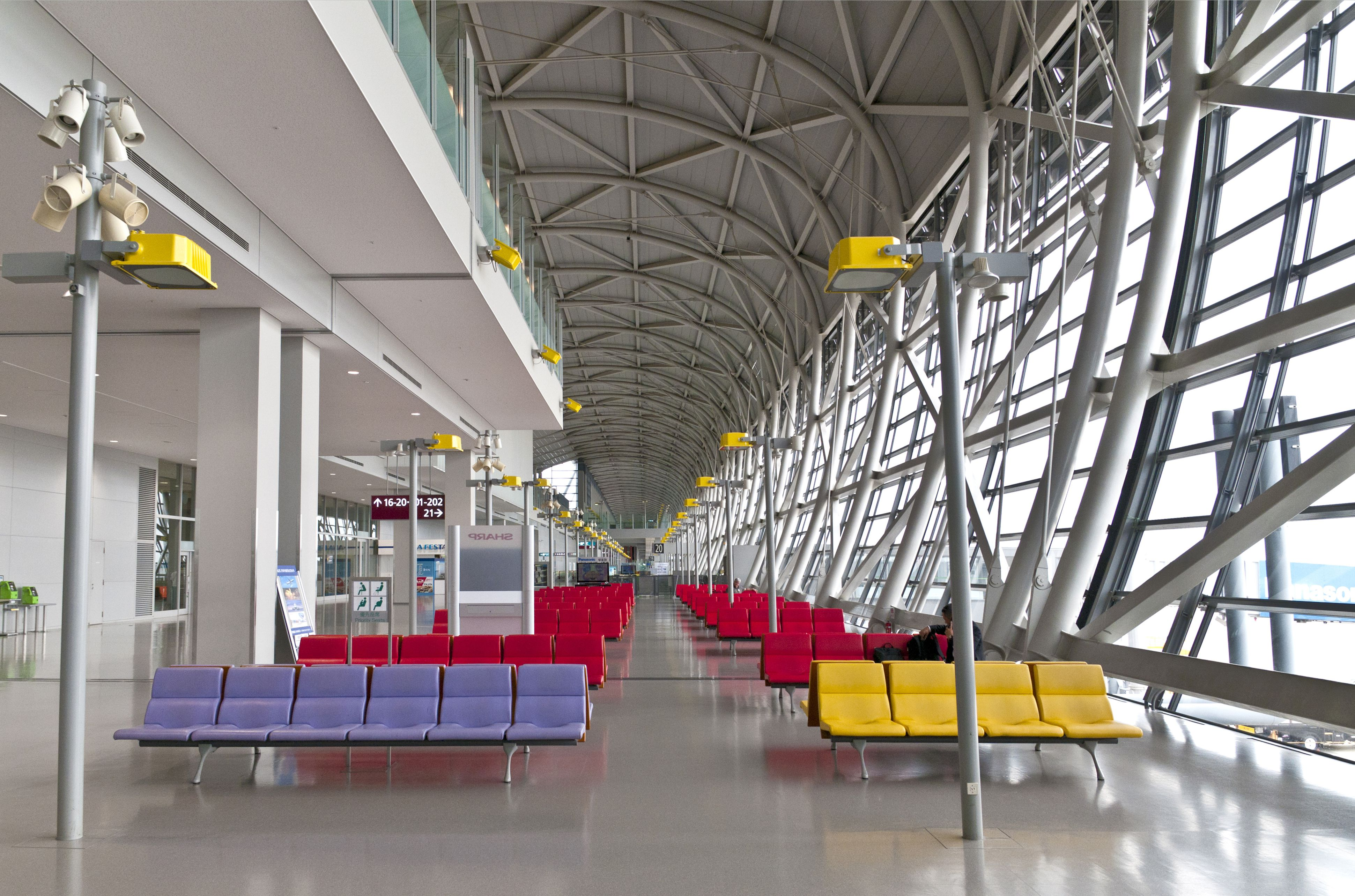 airport terminal seats (blue, red, and yellow) amidst a framework of glass and triangular patterns