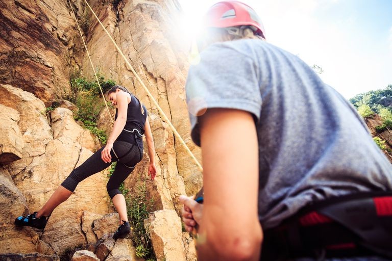 Low Angle View Of Woman Climbing Cliff