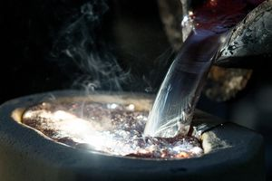 Molten magnesium is poured out of a crucible and into a mold