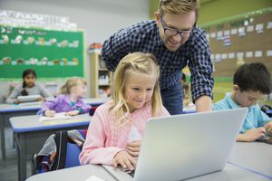 Teacher and elementary student using laptop in classroom